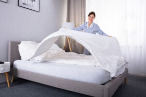 Lone Working Housekeeper Arranging Bedsheet On Bed