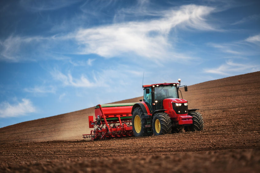 Farmer working on his own in a tractor while seeding crops in a field