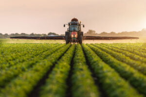 Lone worker in a tractor spraying in a Canadian field